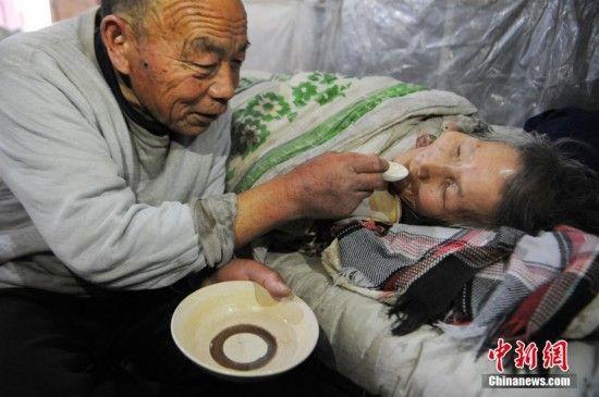 图为2017年2月16日,72岁的蔡广远正在给瘫痪在床上26年的妻子姜占兰喂药。因为近日天气忽冷忽热,姜占兰有些感冒。中新社发 张延林 摄 图片来源:CNSPHOTO