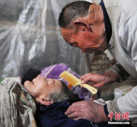 2017年2月16日,72岁的蔡广远正在照顾瘫痪在床上26年的妻子姜占兰。中新社发 张延林 摄 图片来源:CNSPHOTO