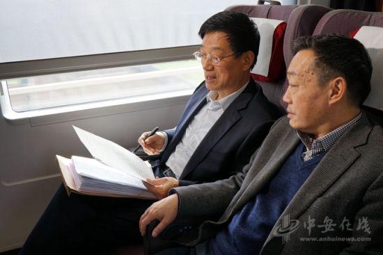 委员在列车上交流提案,查阅资料。