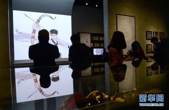 """2月28日,参观者在""""金庸馆""""内欣赏多媒体动画作品。当日,香港首个以著名武侠小说家金庸为主题的常设展馆――""""金庸馆""""在香港文化博物馆揭幕,将于3月1日正式与市民见面。展馆内共展出珍贵手稿、照片、早期小说版本以及各类水墨画等300多项展品,介绍金庸的早期事业、武侠小说创作历程及其小说对香港流行文化的影响。新华社记者秦晴摄"""