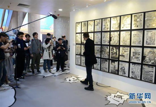 """2月28日,工作人员在""""金庸馆""""水墨画展区介绍作品。当日,香港首个以著名武侠小说家金庸为主题的常设展馆――""""金庸馆""""在香港文化博物馆揭幕,将于3月1日正式与市民见面。展馆内共展出珍贵手稿、照片、早期小说版本以及各类水墨画等300多项展品,介绍金庸的早期事业、武侠小说创作历程及其小说对香港流行文化的影响。新华社记者秦晴摄"""