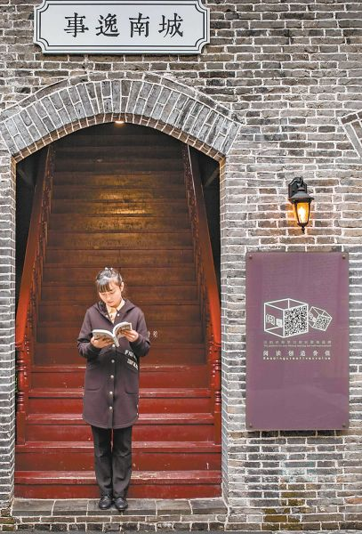 3月21日,读者在安庆劝业场书店门前翻阅刚买的图书。