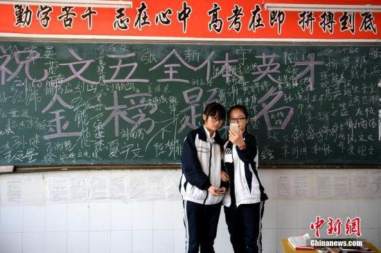 """6月4日,学生在教室里合影留念。每年的此刻,安徽省六安市毛坦厂""""高考镇""""都会重复上演这一时刻,5日,这些高考学子将乘坐大巴去赶考,以冀实现他们的""""大学梦""""。中新社记者韩苏原摄"""