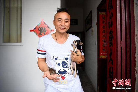"""6月4日,陪读爸爸陈林带着他和他的宠物告别生活一年的地方。每年的此刻,安徽省六安市毛坦厂""""高考镇""""都会重复上演这一时刻,5日,这些高考学子将乘坐大巴去赶考,以冀实现他们的""""大学梦""""。中新社记者 韩苏原 摄"""