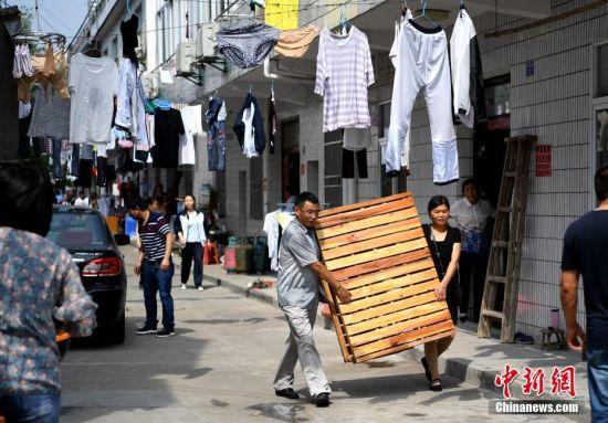 """6月4日,家长打包好行李,准备离开。每年的此刻,安徽省六安市毛坦厂""""高考镇""""都会重复上演这一时刻,5日,这些高考学子将乘坐大巴去赶考,以冀实现他们的""""大学梦""""。中新社记者 韩苏原 摄"""