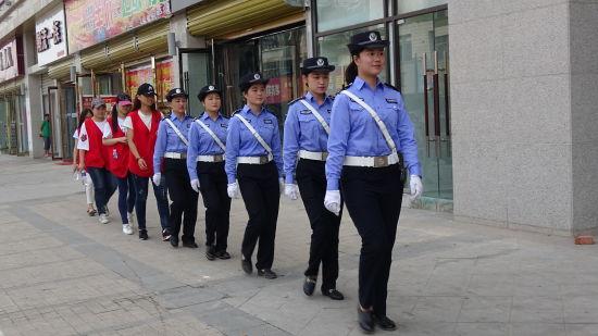 图为大学生志愿者在城管执法人员的带领下徒步巡查浍河路