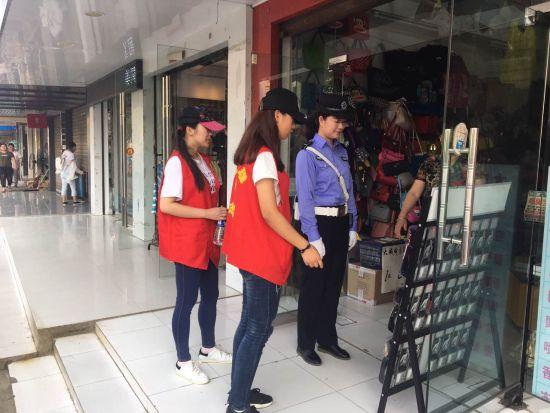 大学生志愿者与城管执法人员清理沿街商铺出店经营等违规经营行为