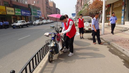 图为大学生志愿者清理东风路随意停放在慢车道的非机动车