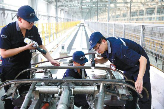 7月13日,合肥南动车运用所车库内,气温高达50℃,地勤机械师正在检查受电弓。本报记者范柏文摄