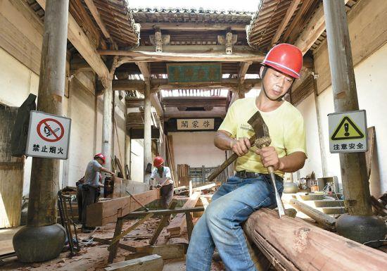 宏村南湖书院里,工人使用传统工具加工木构件。