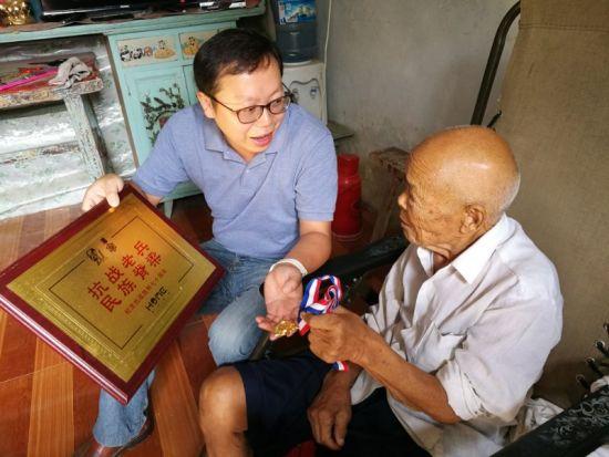 95岁高龄的卞朝清老人向王宏坤一行展示获得的荣誉。