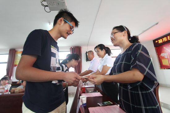 8月26日,在安徽省肥东县店埠镇合浦社区,大一新生王虎等10名学子领到村里发放的20000元助学金 。