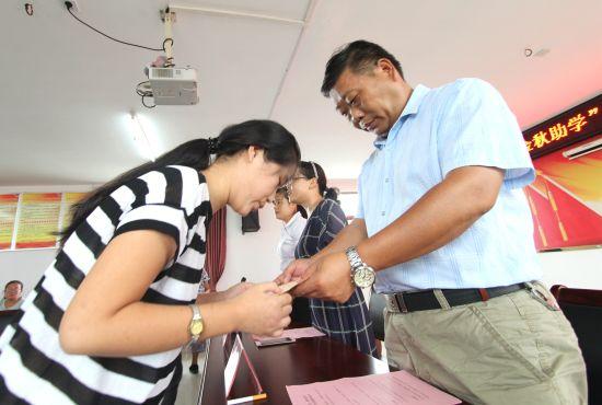 8月26日,在安徽省肥东县店埠镇合浦社区,高三学生许海燕等10名学子领到村里发放的20000元助学金。