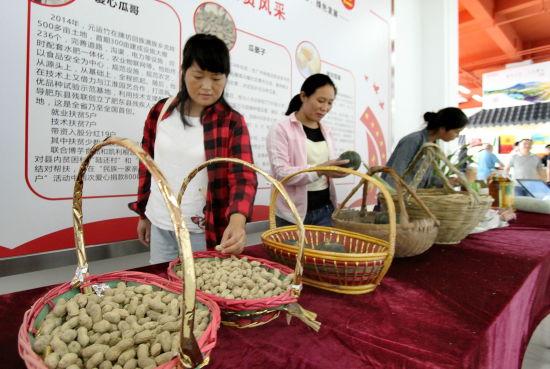 9月12日,在肥东县农产品特色馆扶贫爱心义购展区,客人正在挑选黑花生、贡品小南瓜等农产品。许庆勇 摄