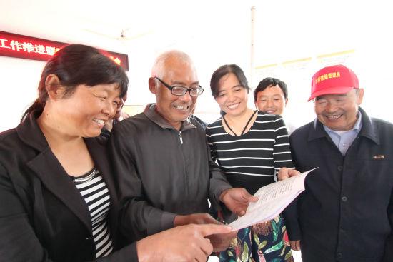 9月29日,在肥东县牌坊回族满族乡高塘社区,当地村民在翻看领到的《村级股份经济合作社股权证》。