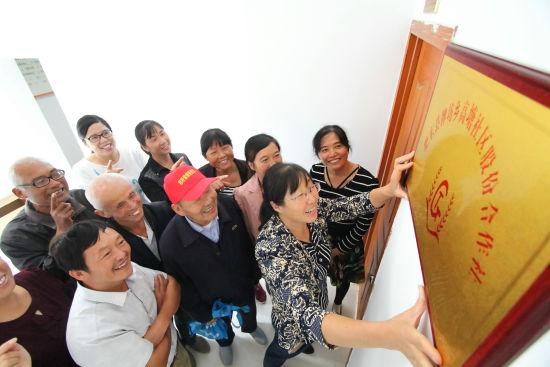 9月29日,在肥东县牌坊回族满族乡高塘社区,当地群众在高兴的张挂 社区股份合作社牌匾。