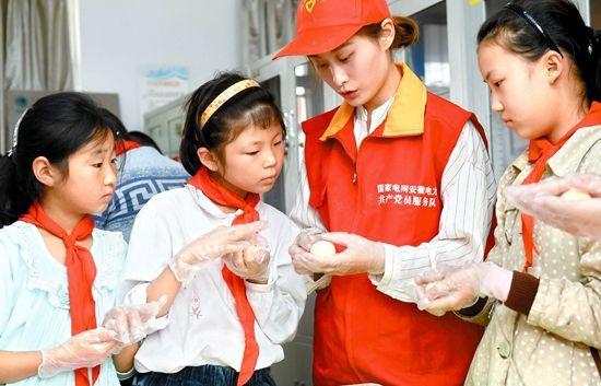 """10月4日,在滁州市南谯区章广小学""""光明驿站"""",志愿者和留守儿童一起制作冰皮月饼。通讯员 宋卫星 摄"""