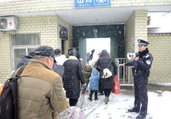 蚌埠铁路公安处涡阳火车站派出所民警在雪中执勤,维持旅客进站秩序