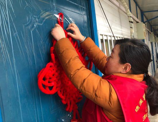社区人员为农民工寝室贴上中国结