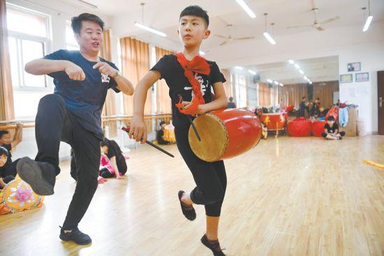 5月27日,在蚌埠淮上区留守儿童艺术培训基地,朱同陆(左)教学生打鼓。