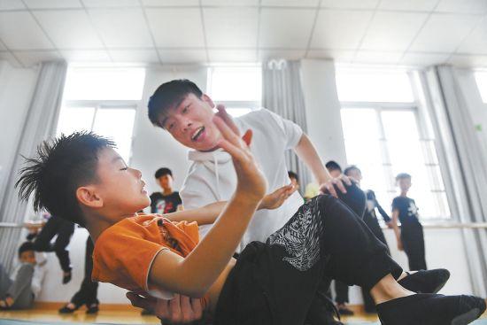 5月27日,在蚌埠市淮上区留守儿童艺术培训基地,周昊给孩子教授技巧基本功。