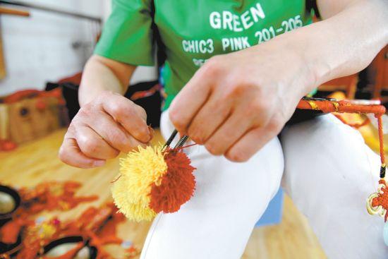 5月28日,在淮上区留守儿童艺术培训基地,史艳丽为孩子们加固演出道具。