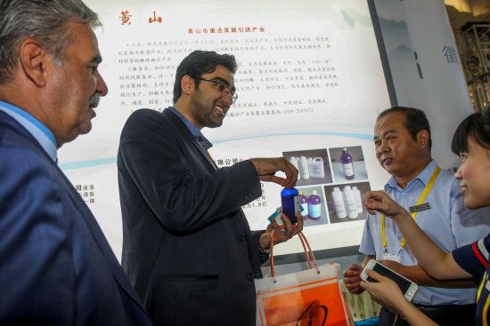 """图为黄山永瑞生物科技有限公司工作人员(右二)向外商企业代表介绍""""纳米银胶体溶液""""新型抗菌剂产品。"""