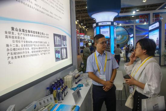 图为黄山永瑞生物科技有限公司工作人员(左一)与国内客商代表交流企业新型抗菌剂产品应用技术。