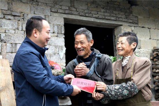 桃源村党总支第一书记、扶贫工作队长王纯在给贫困户发放扶贫红利