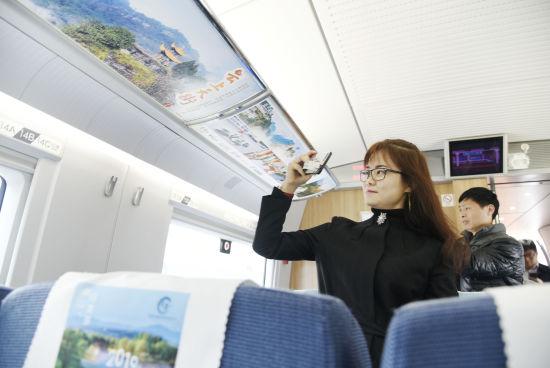 """图为一名乘客用手机拍摄车内""""齐云山景区""""3"""