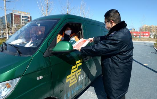 """图为涡阳县税务局窗口工作人员将需要""""邮寄送达""""的资料交给EMS工作人员。"""