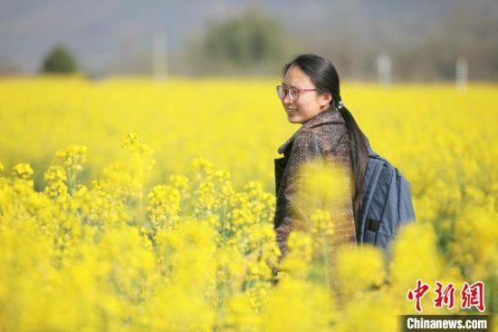 """3月19日,""""美丽中国黄山行 """"系列活动在黄山市黟县石林正式启动。图为南屏村油菜花田里的游客。 樊成柱 摄"""
